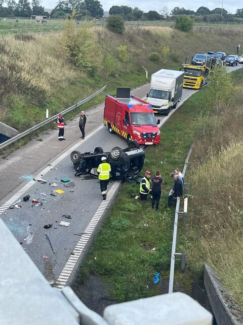 Voldsomt uheld: Bil påkørte autoværn og landede på taget - beredskab massivt til stede